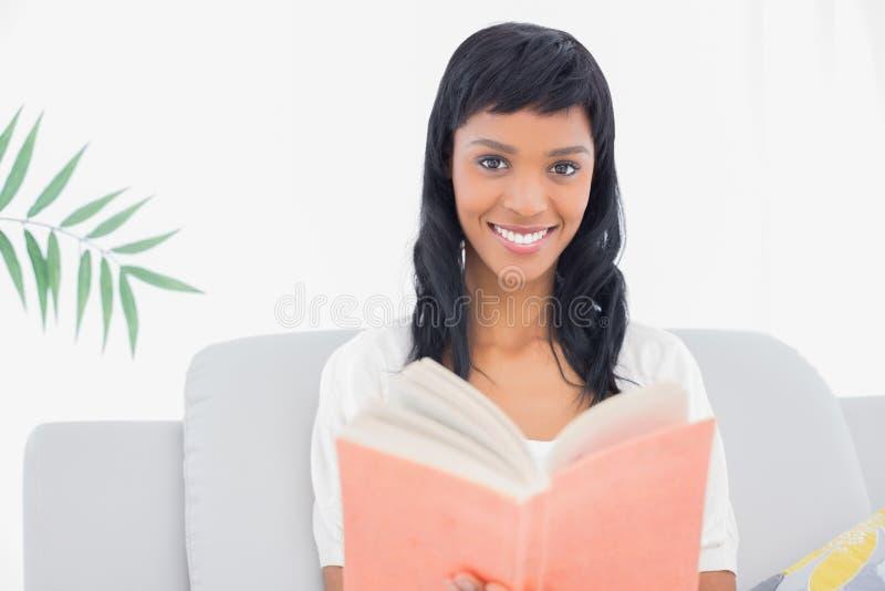 Donna mora adorabile in vestiti bianchi che legge un libro immagini stock