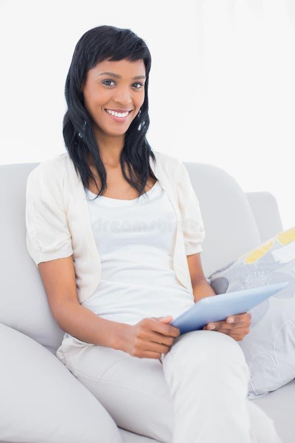 Donna mora adorabile in vestiti bianchi che tengono un pc della compressa fotografie stock libere da diritti