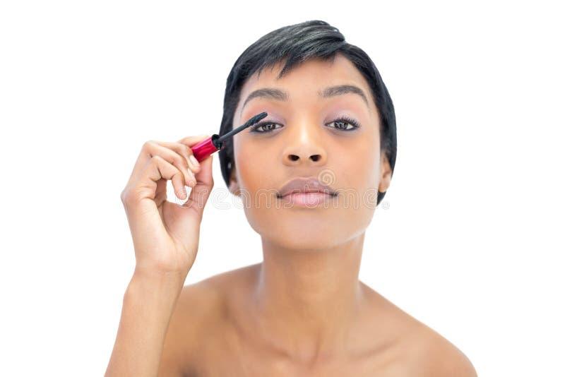 Donna mora concentrata che applica mascara fotografia stock libera da diritti