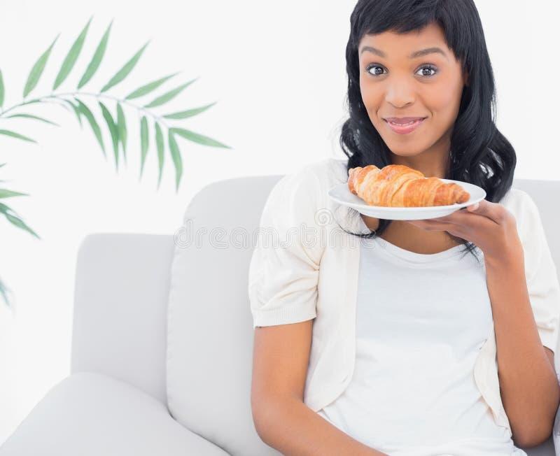 Donna mora divertente in vestiti bianchi che odorano un croissant fotografia stock