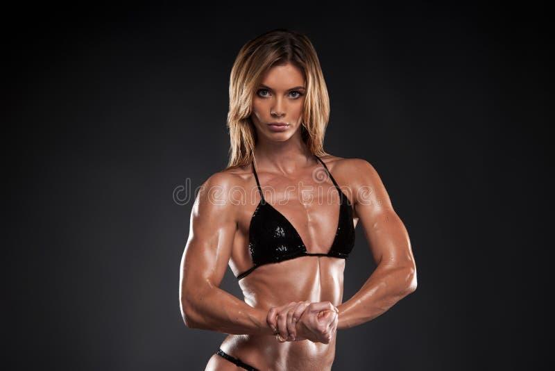 Donna muscolare bionda sexy che posa sulla macchina fotografica. fotografia stock libera da diritti