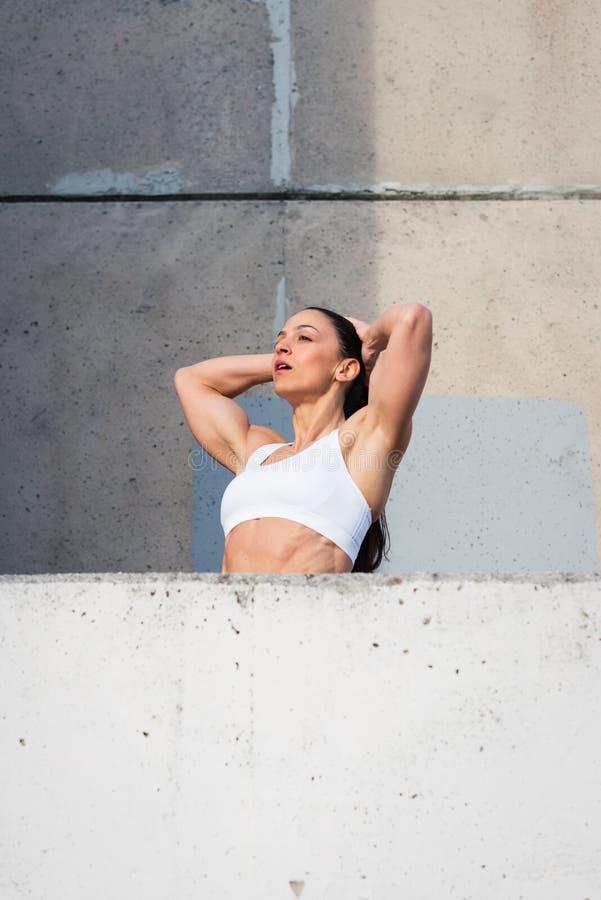 Donna muscolare stanca di forma fisica che riposa dopo l'allenamento urbano immagini stock