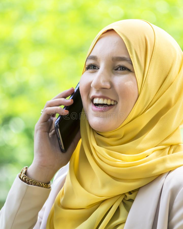 Donna musulmana abbastanza giovane che ha una conversazione sul telefono immagini stock