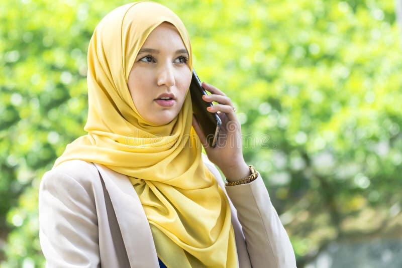 Donna musulmana abbastanza giovane che ha una conversazione sul telefono fotografie stock libere da diritti
