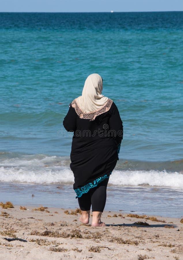 Donna musulmana in abito nero e sciarpa capa di bianco che esaminano fuori la b fotografia stock