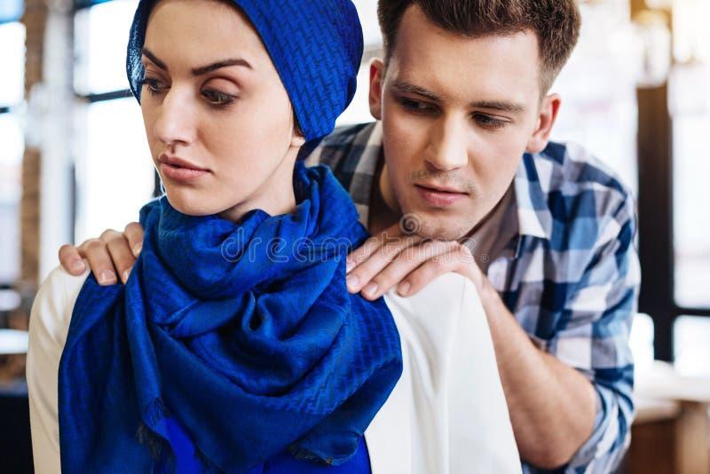 Donna musulmana attraente che avverte umiliazione da un uomo fotografie stock libere da diritti