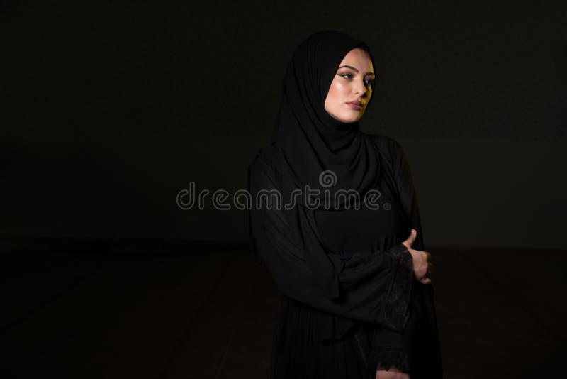 Donna musulmana attraente su fondo nero immagini stock