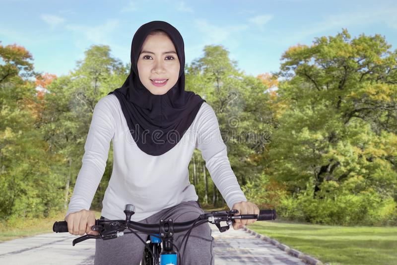 Donna musulmana che cicla sul parco fotografia stock