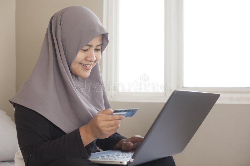 Donna musulmana che fa acquisto online fotografie stock libere da diritti