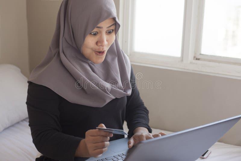 Donna musulmana che fa acquisto online immagini stock libere da diritti