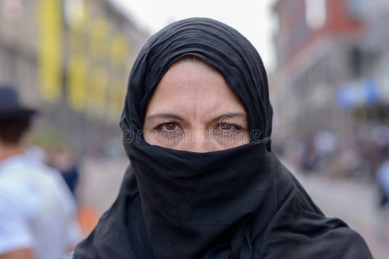 Donna musulmana che indossa un hijab nero in città fotografia stock libera da diritti
