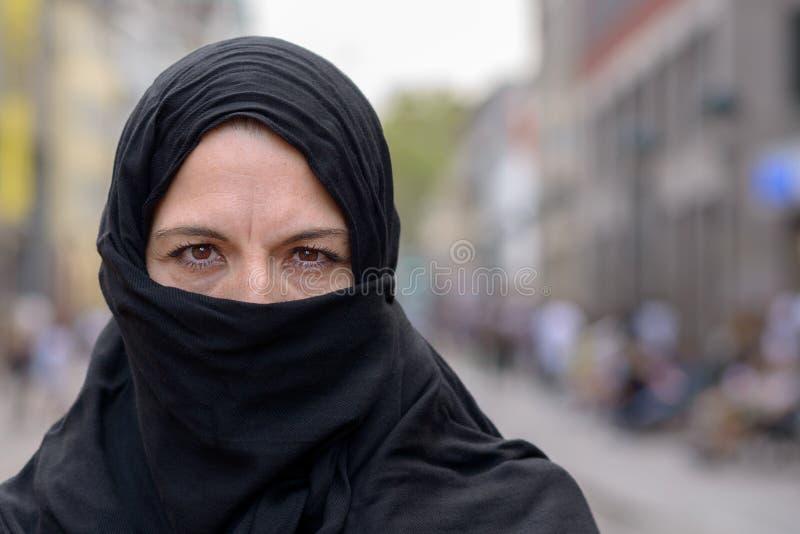 Donna musulmana che indossa un hijab nero in città fotografie stock libere da diritti
