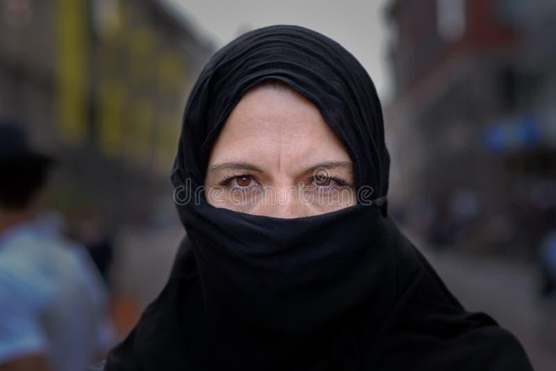 Donna musulmana che indossa un hijab nero in città immagini stock
