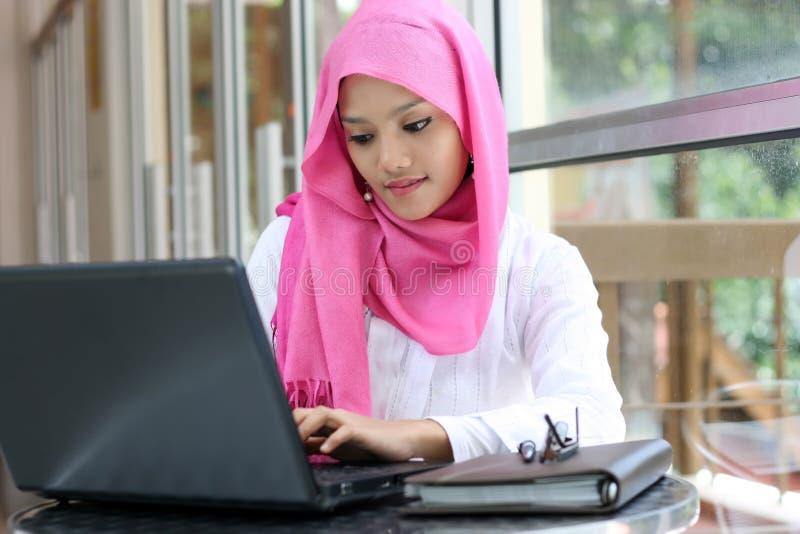 Donna musulmana che per mezzo del computer portatile fotografia stock libera da diritti