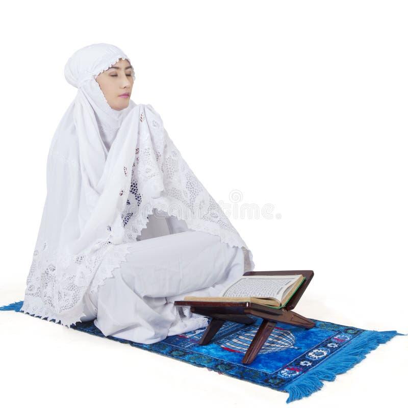 Donna musulmana che prega con il Corano immagini stock