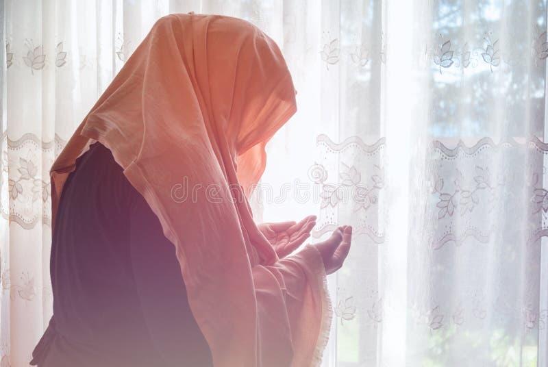 Donna musulmana con pregare del hijab dell'interno alla finestra luminosa fotografia stock