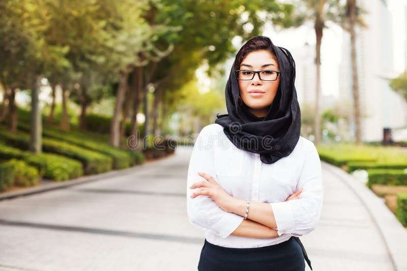 Donna musulmana corsa mista su una via della città del Dubai fotografie stock