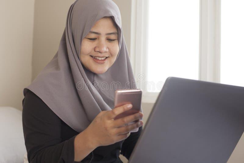 Donna musulmana felice che lavora con il computer portatile e lo Smart Phone nella sua camera da letto immagini stock