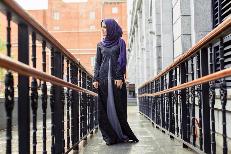 Donna musulmana moderna in bello vestito orientale che sta sui precedenti dell'hotel fotografie stock libere da diritti