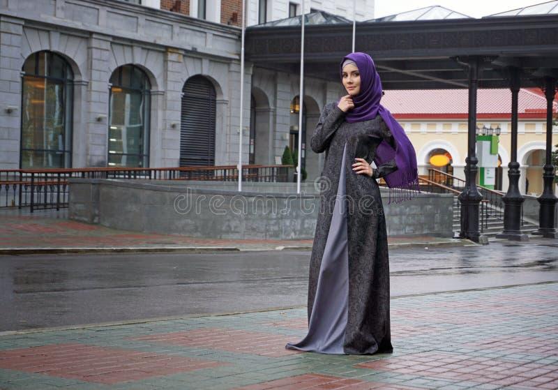 Donna musulmana moderna in bello vestito orientale che sta sui precedenti dell'hotel fotografia stock libera da diritti