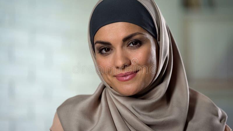 Donna musulmana modesta nel hijab che esamina macchina fotografica con il sorriso misterioso, primo piano immagini stock libere da diritti