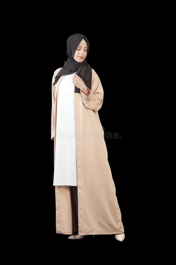 Donna musulmana in un bello vestito islamico nella piena crescita, isolata su un fondo nero fotografie stock libere da diritti