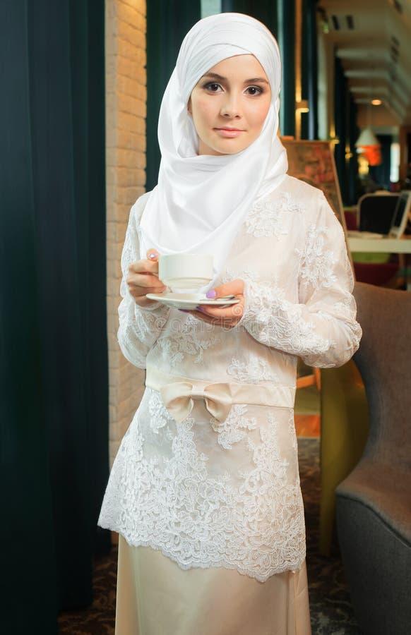 Donna musulmana in un vestito da sposa bianco con una tazza di tè in sue mani fotografia stock libera da diritti