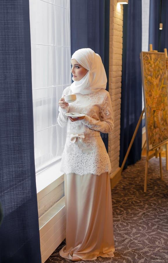 Donna musulmana in un vestito da sposa bianco con una tazza di tè in sue mani fotografia stock