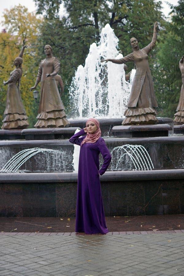 Donna musulmana in una bella passeggiata islamica del vestito in un parco della città immagini stock