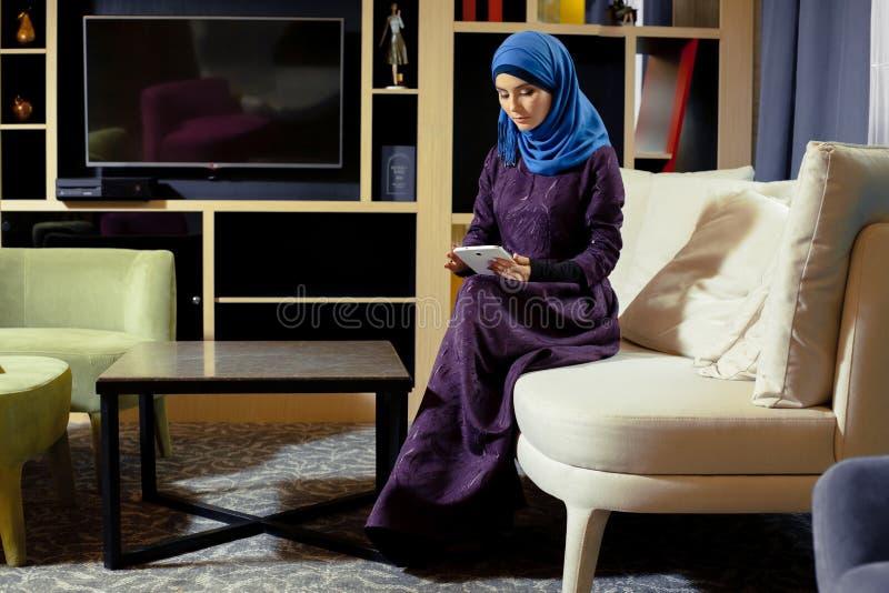 Donna musulmana in vestiti orientali contemporanei che si siedono sullo strato e che funzionano con la compressa elettronica immagine stock libera da diritti