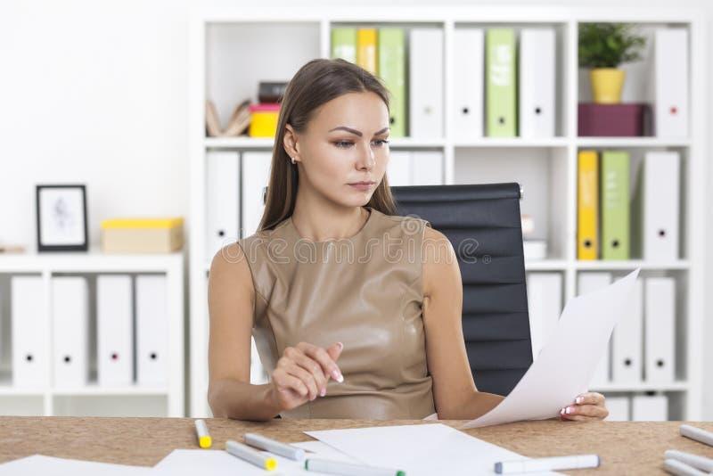 Donna nei documenti beige della lettura immagini stock