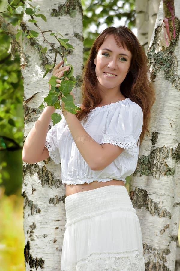 Donna nel bianco dalla betulla di estate fotografia stock