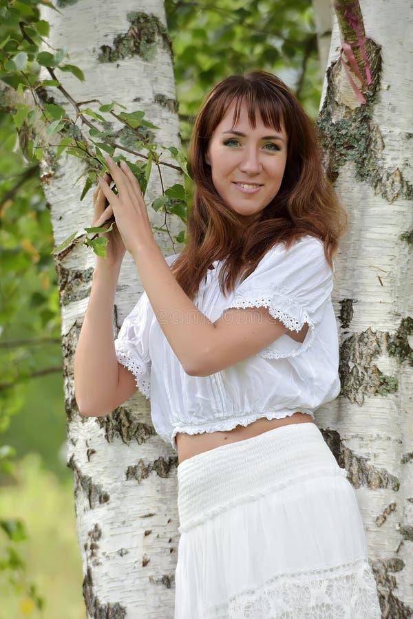 Donna nel bianco dalla betulla di estate immagini stock libere da diritti