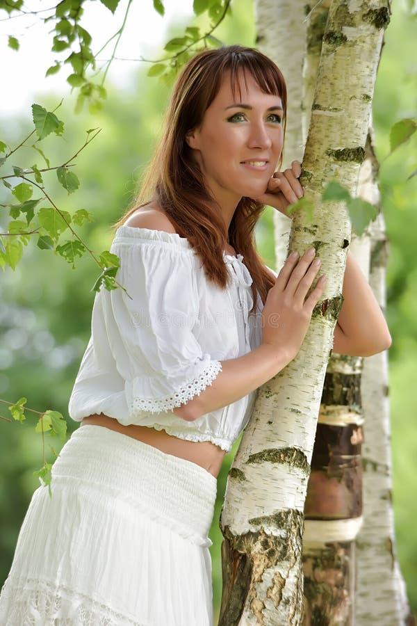 Donna nel bianco dalla betulla di estate fotografie stock libere da diritti