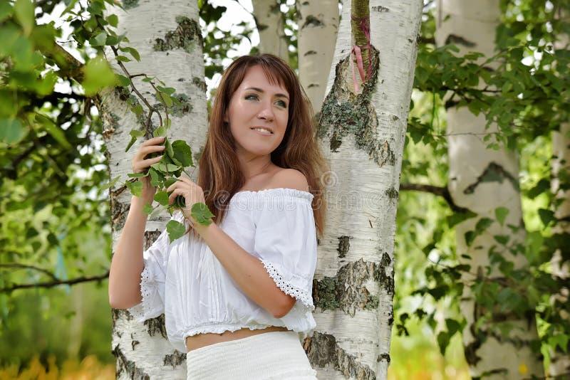 Donna nel bianco dalla betulla di estate fotografia stock libera da diritti