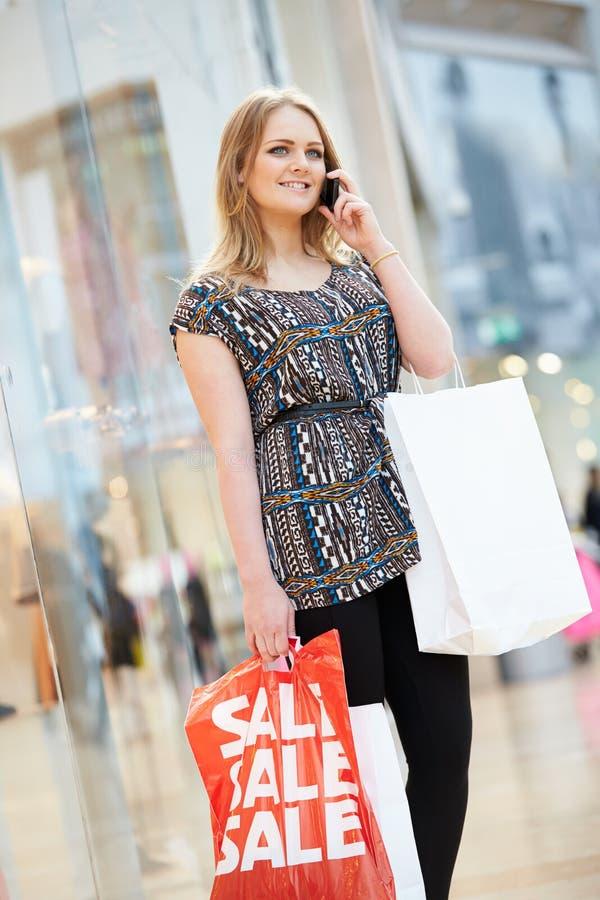 Donna nel centro commerciale facendo uso del telefono cellulare fotografie stock libere da diritti