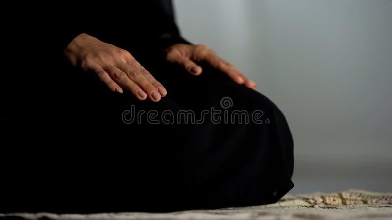 Donna nel hijab nero tradizionale che si inginocchia sulla moschea della stuoia di preghiera, cultura islamica fotografie stock libere da diritti