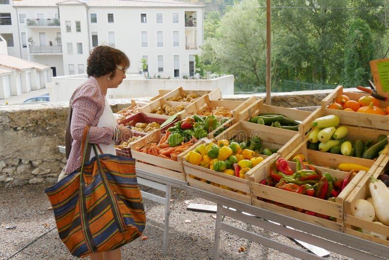 Donna nel mercato delle verdure immagine stock