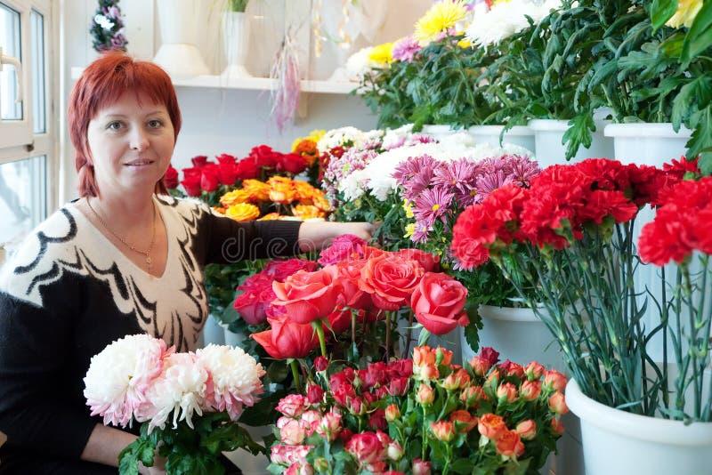 Donna nel negozio di fiori fotografia stock