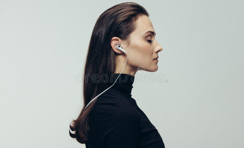 Donna nel nero con le cuffie fotografie stock