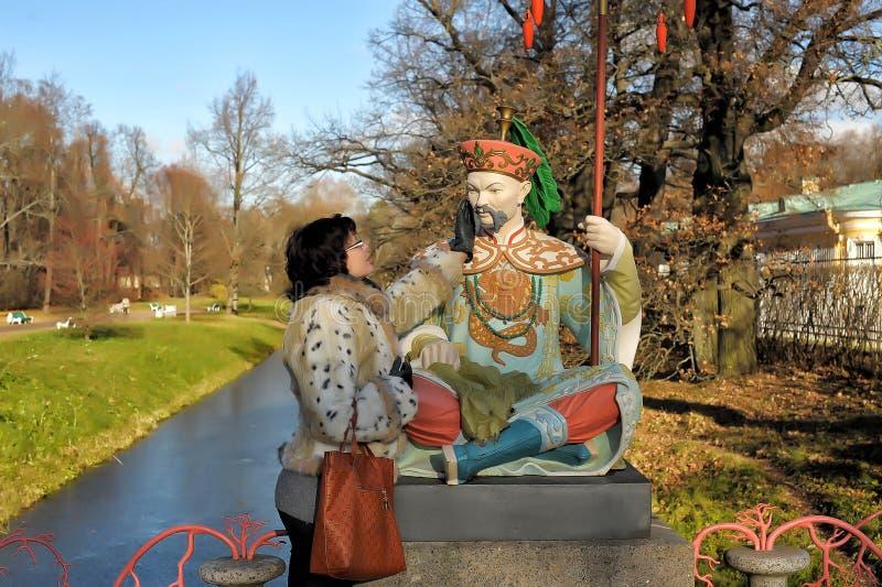 Donna nel parco di autunno accanto alla scultura fotografia stock