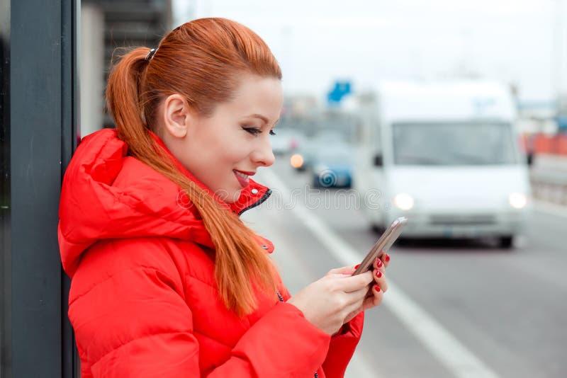 Donna nel profilo che tiene un telefono, mandante un sms ad un esterno degli sms su un Bu fotografie stock