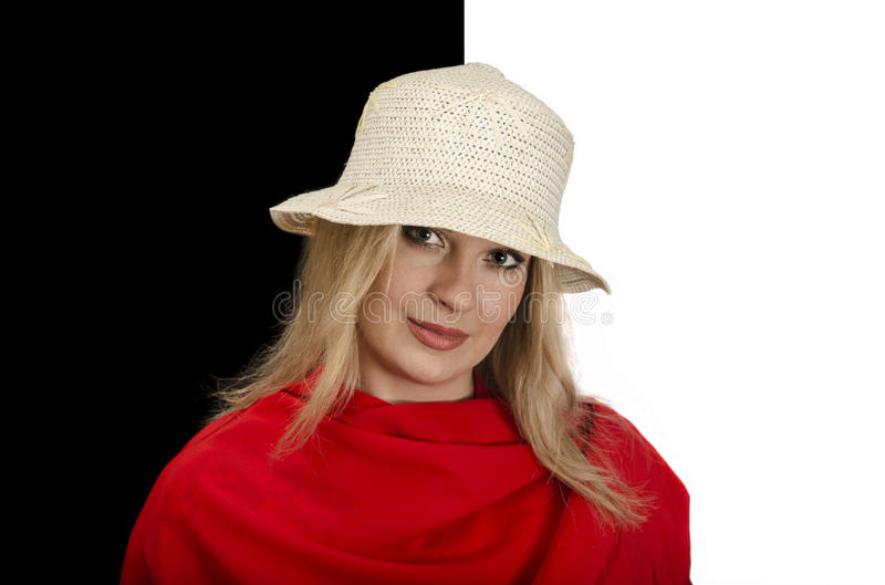 Donna nel rosso, portante un cappello di paglia, un fondo in bianco e nero fotografia stock libera da diritti
