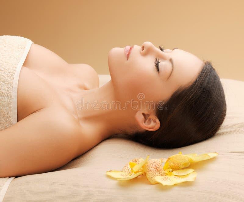 Donna nel salone della stazione termale che si trova sullo scrittorio di massaggio immagini stock libere da diritti