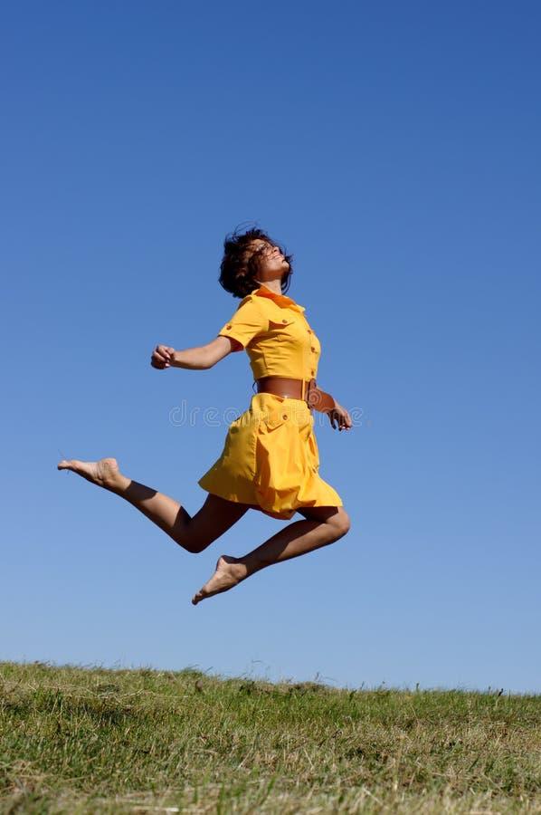 Donna nel salto giallo del vestito immagini stock