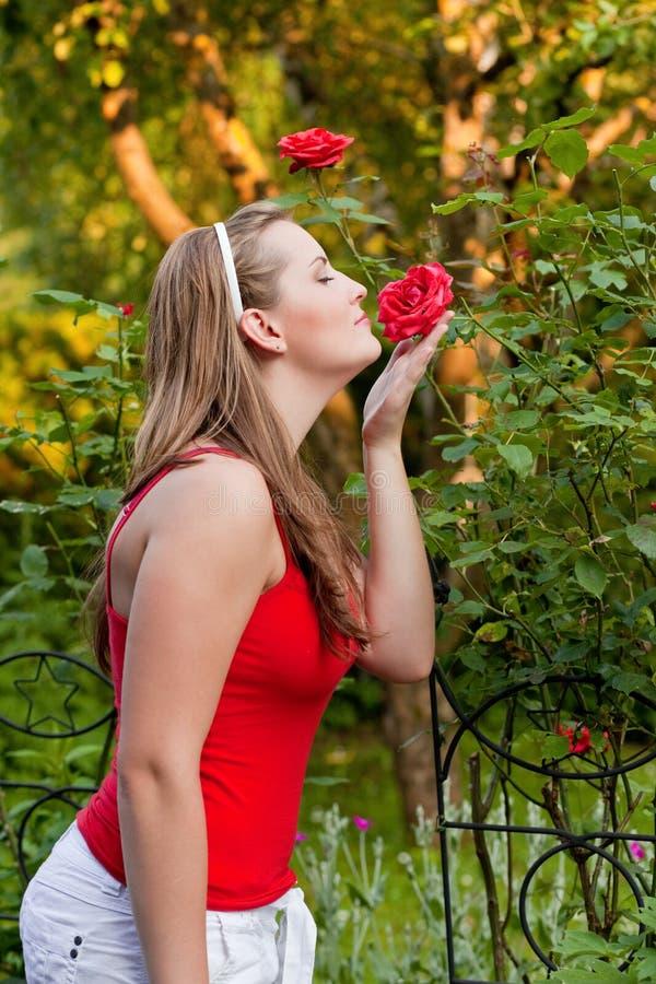 Donna nel suo giardino che fiuta alle rose immagine stock