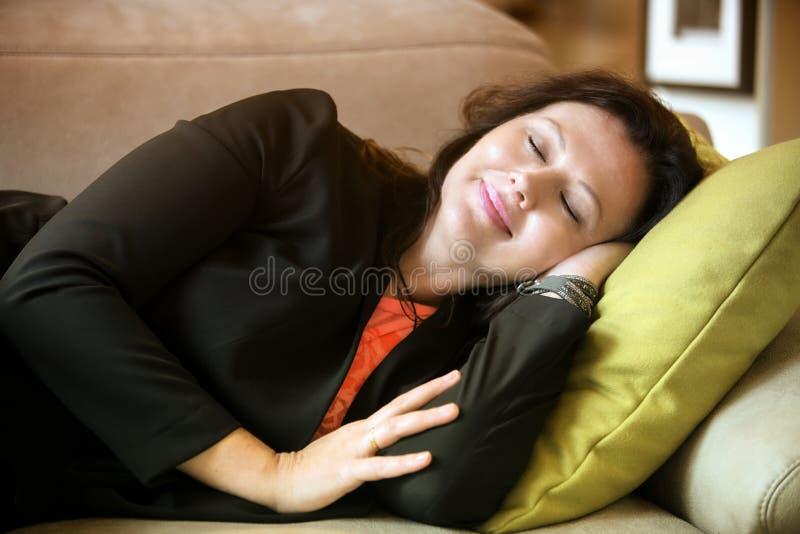 Donna nel suo 40s che dorme sullo strato fotografie stock libere da diritti