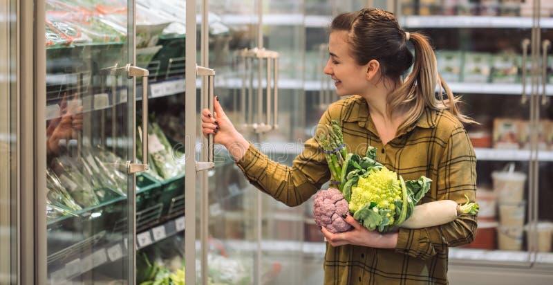 Donna nel supermercato La bella giovane donna tiene nelle verdure organiche fresche delle mani ed apre il frigorifero nel superme fotografia stock