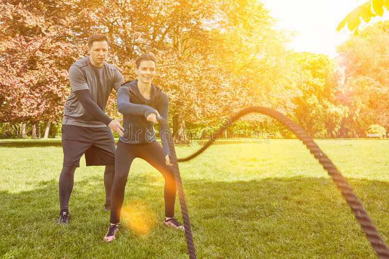 Donna nell'addestramento di forma fisica della corda di battaglia fotografie stock libere da diritti
