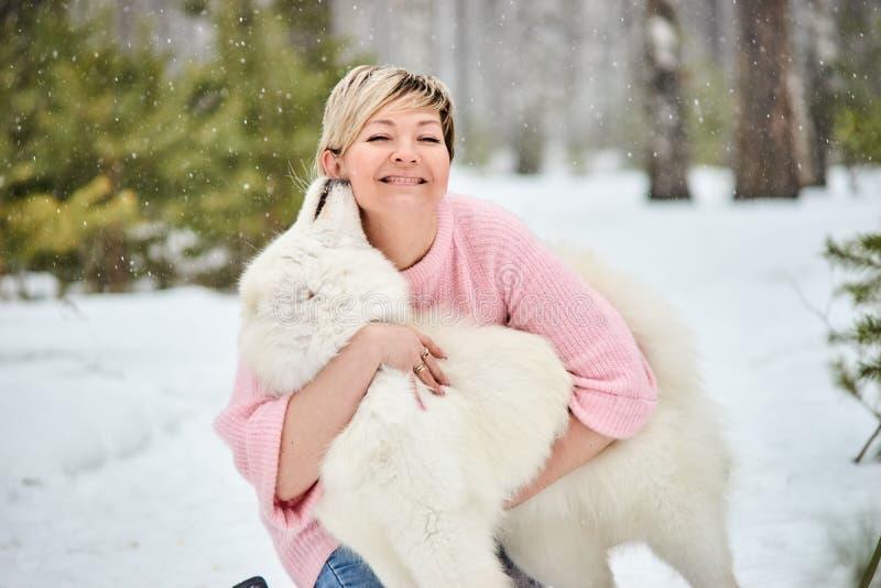 Donna nella foresta di inverno che cammina con un cane La neve sta cadendo immagini stock